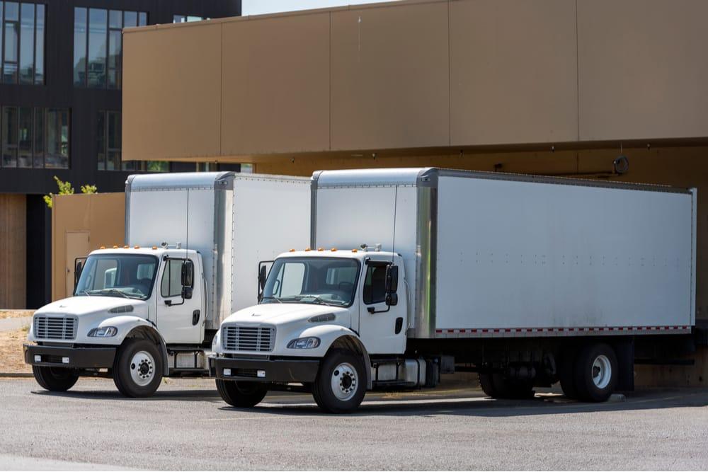 Two white box trucks, also called straight trucks