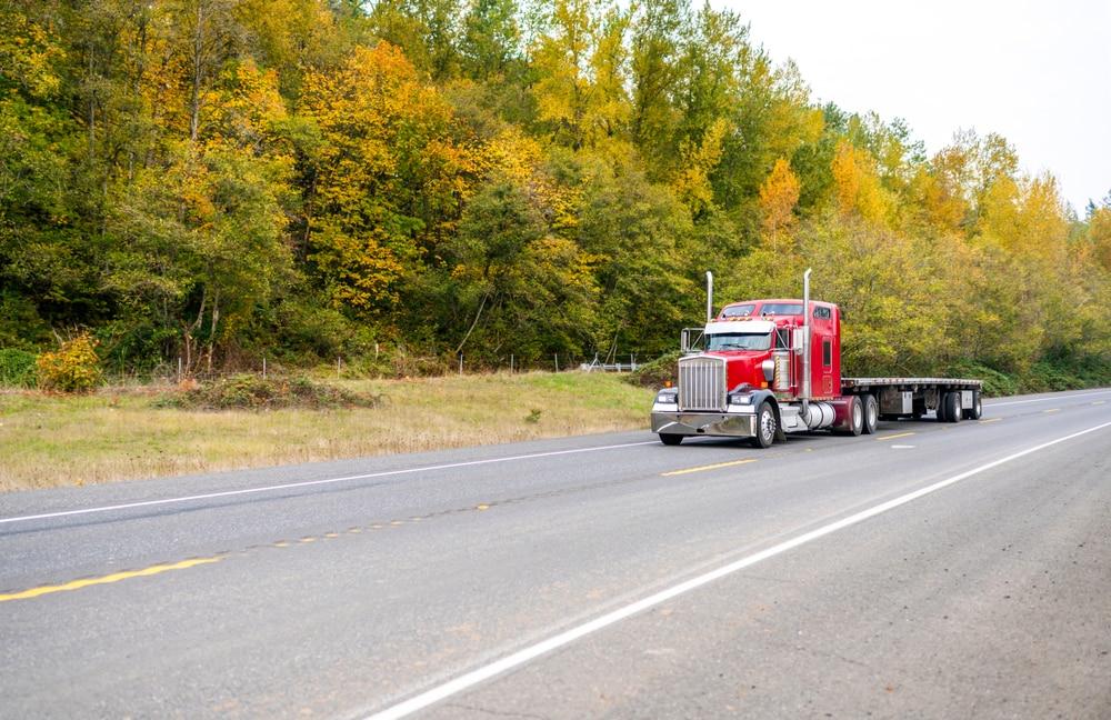 A flatbed truck, a type of semi-trucks/CMVs with a flat platform